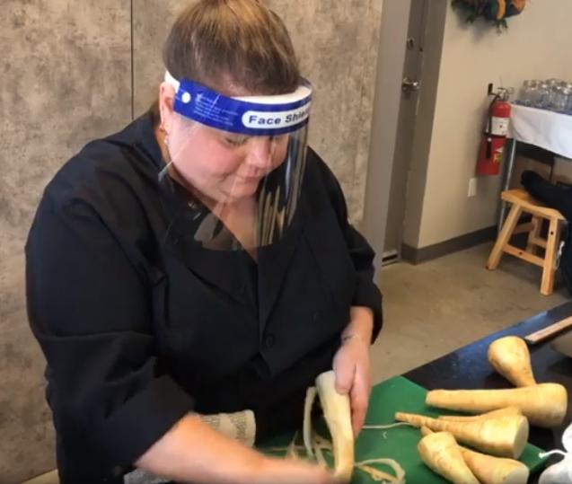woman wearing ppe peeling parsnips