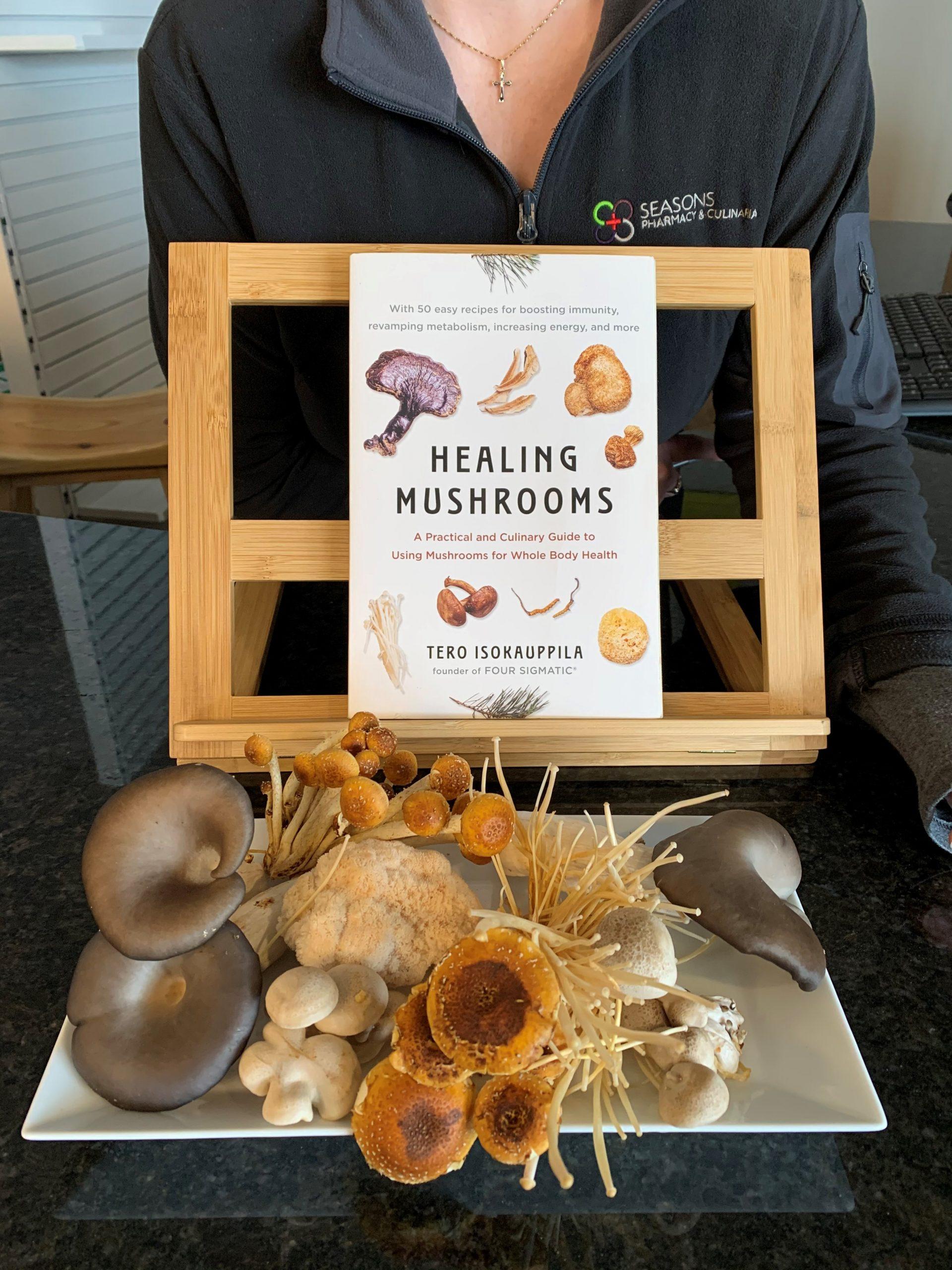 "selection of mushrooms in front of ""healing Mushrooms"" book"