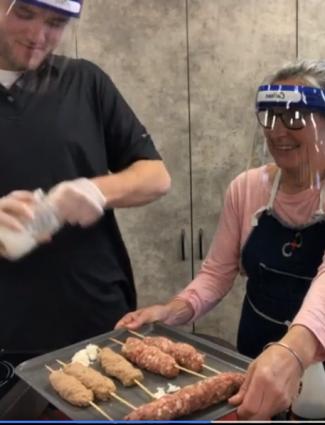 pork being prepared into skewers by people wearing ppe